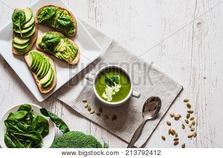 Vegetarian healthy food. Soup and vegan sandwiches. Different sandwiches with avocado. Brunch on white wooden background.