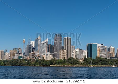 Sydney Australia - March 26 2017:Tall office towers skyline seen off the water under blue sky. Small white yachts and Botanical garden.
