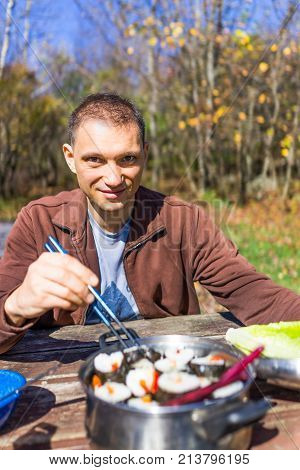Portrait of young man smiling sitting on wooden picnic table in campground with chopsticks ready to eat sushi during autumn camping trip