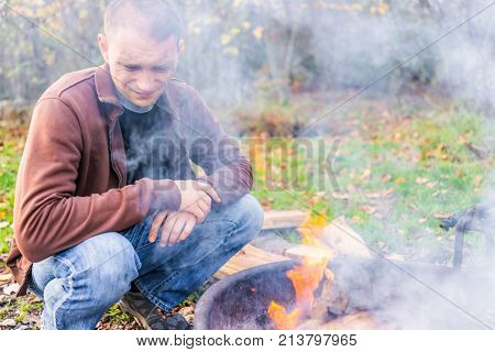 Young Dirty Gritty Man With Face Covered In Grey Ash Blowing Campfire Bonfire Flame In Fire Pit Fril