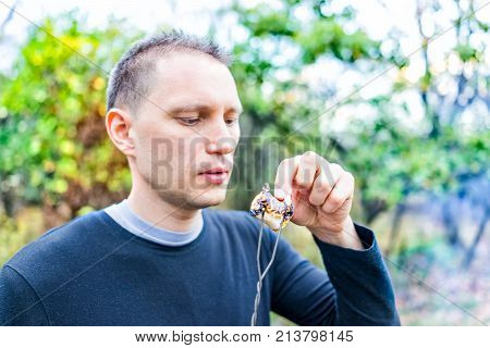 Young Man Peeling Charred Skin On Roasted Caramelized Marshmallow Skewer Closeup Portrait