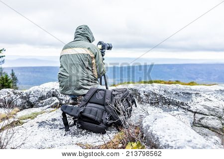 Standing Young Man Photographer With Camera, Gear, Backpack And Tripod On Cold Autumn Morning In Jac
