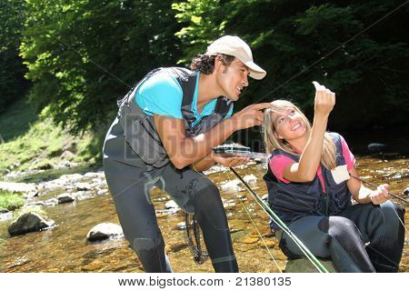 Couple looking at fishing flies in river