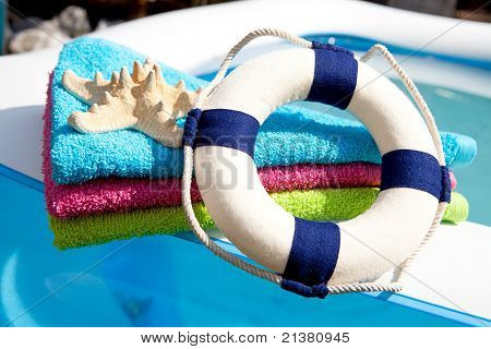 Colorful Towel, Life Buoy And Starfish By The Swimpool