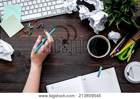 Clutter in office. Desk covered with crumpled paper and coffee stains. Dark wooden background top view.