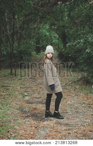 Outdoors lifestyle fashion portrait of pretty young woman walking on the autumn park. Holding maple leaves. Wearing stylish grey coat, sunglasses and glovelettes. Enjoying autumn nature. Autumn colors