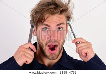 Maintenance And Repairing Concept. Man Holds Wrench Tools Near Face