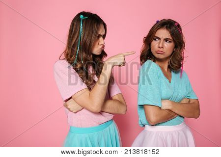 Close-up portrait of offended brunette woman pointing with finger on her friend, isolated on pink background