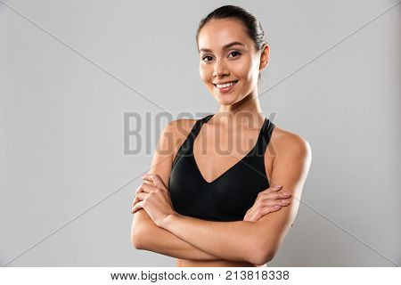 Image of amazing young sports woman posing isolated over grey background. Looking camera with arms crossed.