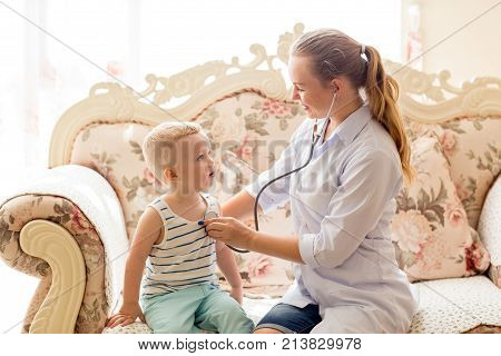 Portrait of young Caucasian female doctor wearing glasses and lab coat sitting on coach and listening to heartbeat of little boy with stethoscope. Pediatrics and health concept