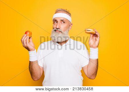 Athlete Cool Grandpa Holds Forbidden Junkfood Cheeseburger And Fruit. Weightloss, Decision, Motivati