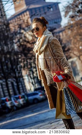 Rediscovering things everybody love in Milan. young traveller woman with shopping bags and Christmas gift in Milan Italy walking