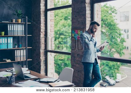 Ponder Fashionable Brunet Bearded Lawyer Is Looking At The Screen Of Device, His Tablet, Standing In