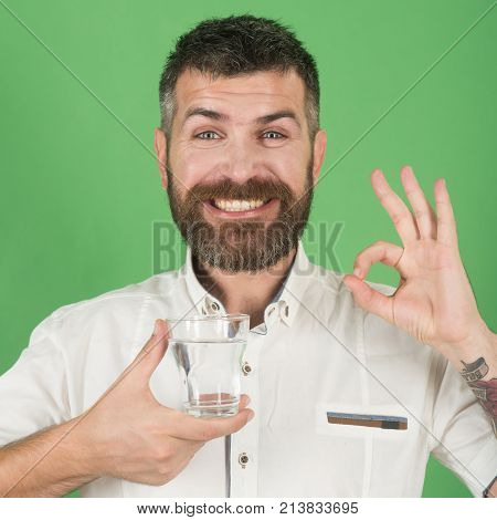 Man With Long Beard Hold Water Glass On Green Background.