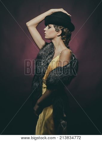Look and retro style pinup. Pin up pretty fashion model pose on burgundy background. Woman with stylish retro hair and makeup. Girl in fashionable yellow dress hat fur. Beauty and vintage fashion.