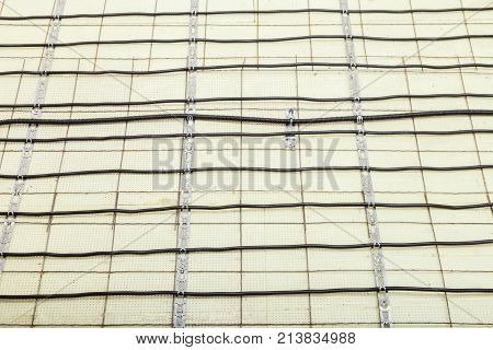 Electric floor heating system installation in new house electric heating cable is installed on the reinforcement grid with the help of mounting tape on the plates of expanded polystyrene