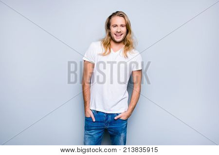 Handsome Careless Smiling Young Guy With Long Blonde Hair, Clothes In White Tshirt And Blue Jeans Is