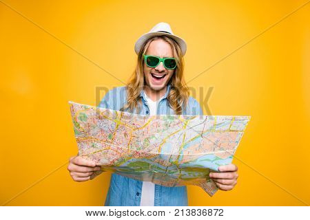 Oh No! Portrair Of Young Shocked Man Looking In Open Road Map On Yellow Background. A Tourist On Sum
