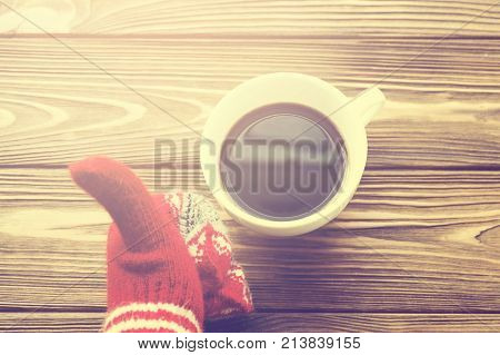 Top view of hand into the knitted gloves showing thumbs up sign and the cup of coffee on wooden background, toning beige tones. Concept of Happy New Year, winter time and comfort