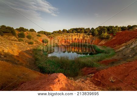 This lake was a Bauxite (mineral used to produce aluminium) mine until 1976 when it has been abandoned due to the infiltration of salted water coming from the sea that has created the lake. It is located in Otranto a city of the Puglia region Italy.  poster