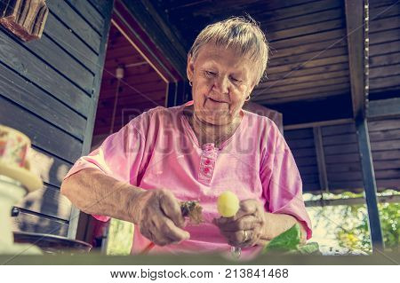 Senior woman pealing potatoes. Granny cooking delicous food.