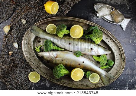 perch on a silver platter with broccoli and lemon