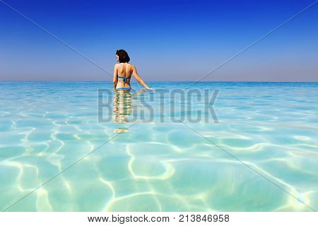 Happy girl on topical beach view from back. Young woman stands in the sea in Dubai resort. Tropical resort backgroud.