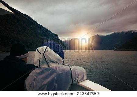 Middle aged couple admiring stunning scenery during Norway in a nutshell sightseeing cruise through the Aurlandsfjord and  narrow Naeroyfjord