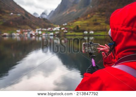 Tourist taking pictures on a smartphone of beautiful fjords during Norway in a nutshell sightseeing cruise through the magnificent Aurlandsfjord and the narrow Nærøyfjord poster