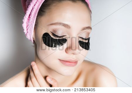 beautiful young girl with clean skin, with a pink towel on her head, under the eyes of black silicone patches, eyes closed