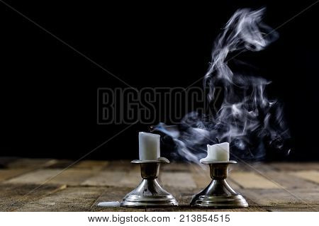 Blown candles in silver candlesticks with smoked wick. Smoke from a wick on a black background. Wooden table poster