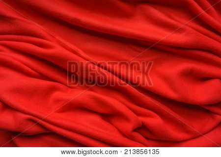 Red fabric fleece, wave, draperies. Beautiful textile backdrop. Close-up. Top view