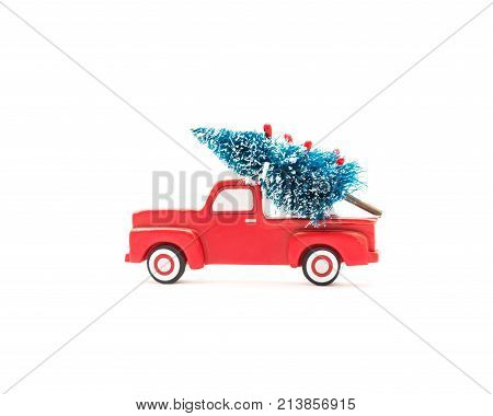 Christmas tree on sturdy toy pickup truck. Wooden car carrying a artificial Xmas tree ornament. Christmas holiday celebration concept. A great addition to any holiday decor. poster