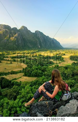 Young woman enjoying the view of farm fields in Vang Vieng Laos. Vang Vieng is a popular destination for adventure tourism in a limestone karst landscape.