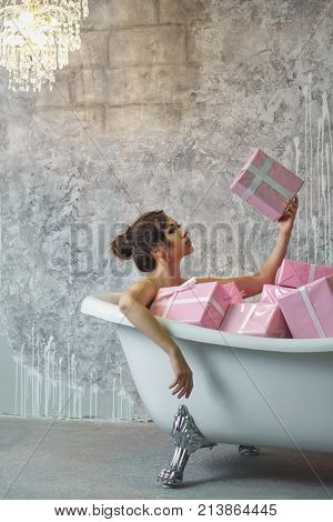Young attractive girl is sitting in the bath with gifts. She is bathing in Christmas presents with a sale. The girl chooses which gift to open first.