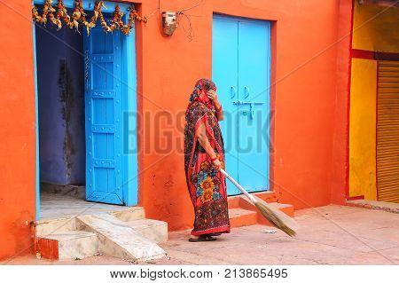 Local woman sweeping yard in Taj Ganj neighborhood of Agra Uttar Pradesh India. Agra is one of the most populous cities in Uttar Pradesh
