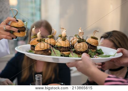 Mini burger on the plate. Woman taking mini burger from the catering sevise waiter plate on the event.
