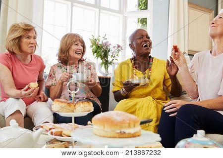 Senior Female Friends Enjoying Afternoon Tea At Home Together