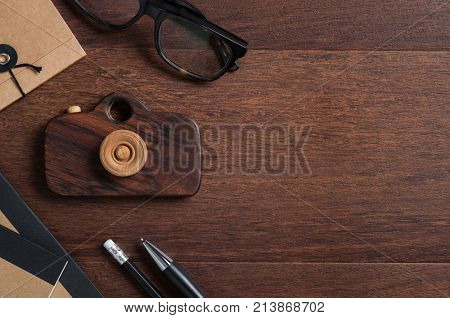 High angle view of photographer desk with office equipment and spectacles. Top view of vintage style wooden table with eyewear, recycled notepad and wooden camera. Traveler desk with copy space.