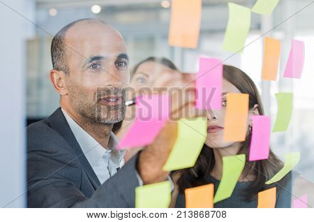 Business team having a meeting in the office using colored sticky notes for plan. Senior manager planning new strategy with teamowrk. Mature businessman working with colleagues in a conference room.