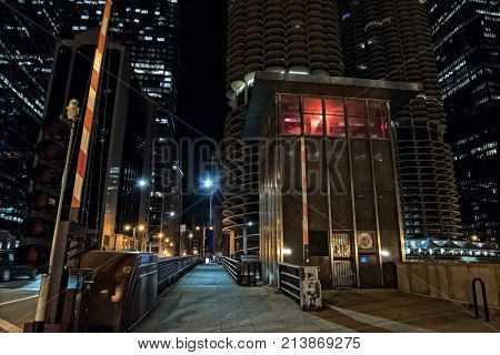 Chicago urban vintage river drawbridge with tender house and marina city towers at night.