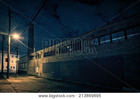 Scary dark city Chicago alley at night next to an urban factory with smokestack.