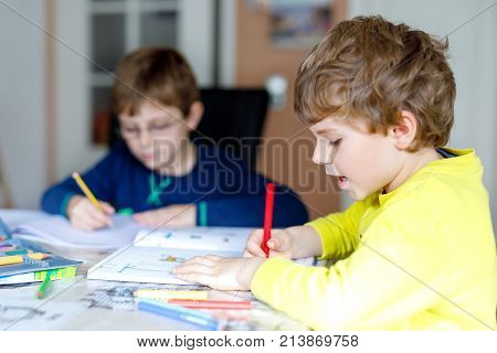 Two little kids boys at home making homework. Little concentrated children writing with colorful pencils, indoors. Elementary school and education. Siblings and best friends learning