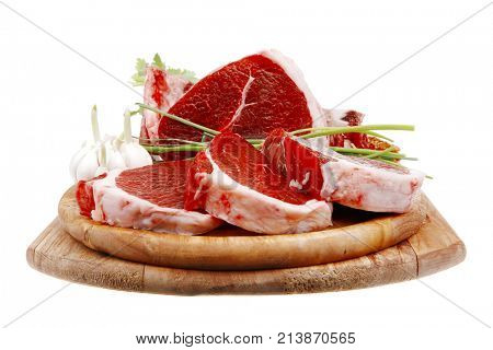 fresh meat : raw uncooked fat lamb pork rib and fillet with green stuff and red chili pepper on wooden plate isolated over white background