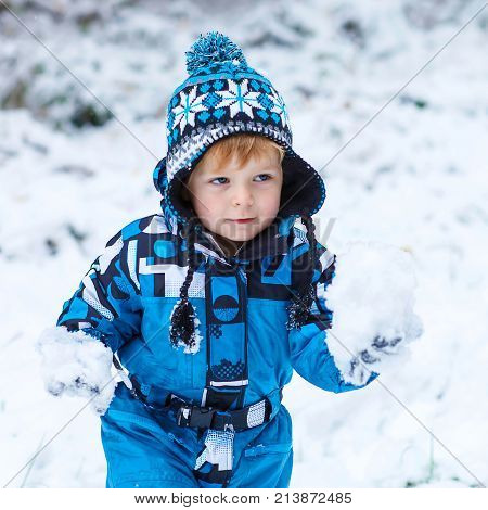 Winter portrait of kid boy in colorful clothes, outdoors during snowfall. Active outoors leisure with children in winter on cold snowy days. Happy toddler child having fun with snow in forest