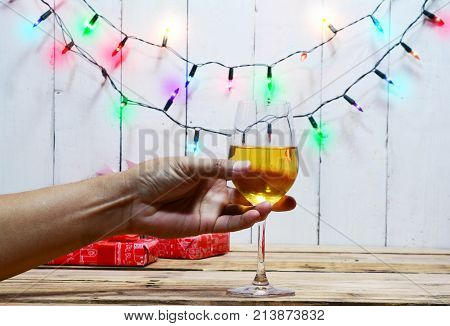 Celebration On Christmas . Adult Hand Holding Wine Glass , Gift Boxes  On Wood Table With Electric B