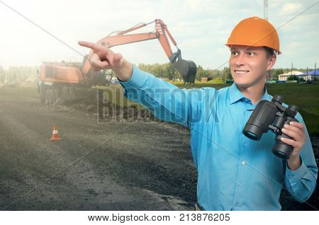 Road construction builder in a hardhat holding in hat binoculars and shows by his another hand the way where a new road will be built or repair. Road construction concept.