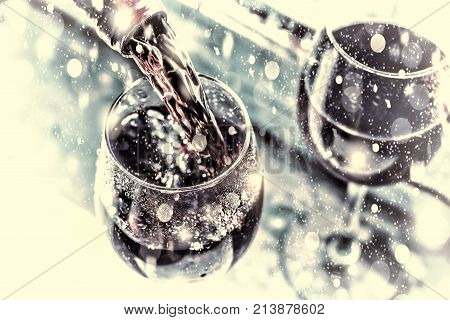 Christmas, New Year. Pouring Red Wine. Wine In A Glass. Selective Focus, Motion Blur, Red Wine In A