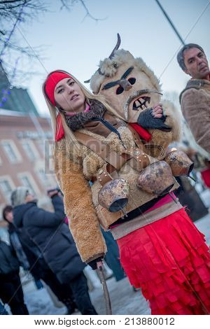 PERNIK, BULGARIA - JANUARY 27, 2017: Beautiful kuker girl carrying big brass ritual bells is holding her scary mask at Surva, the International Festival of the Masquerade Games