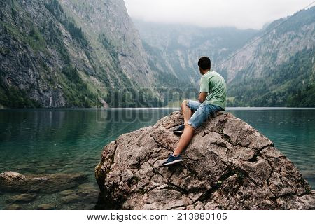 Young adult man sitting on rock looking at beautiful and misty lake in the alps. Obersee
